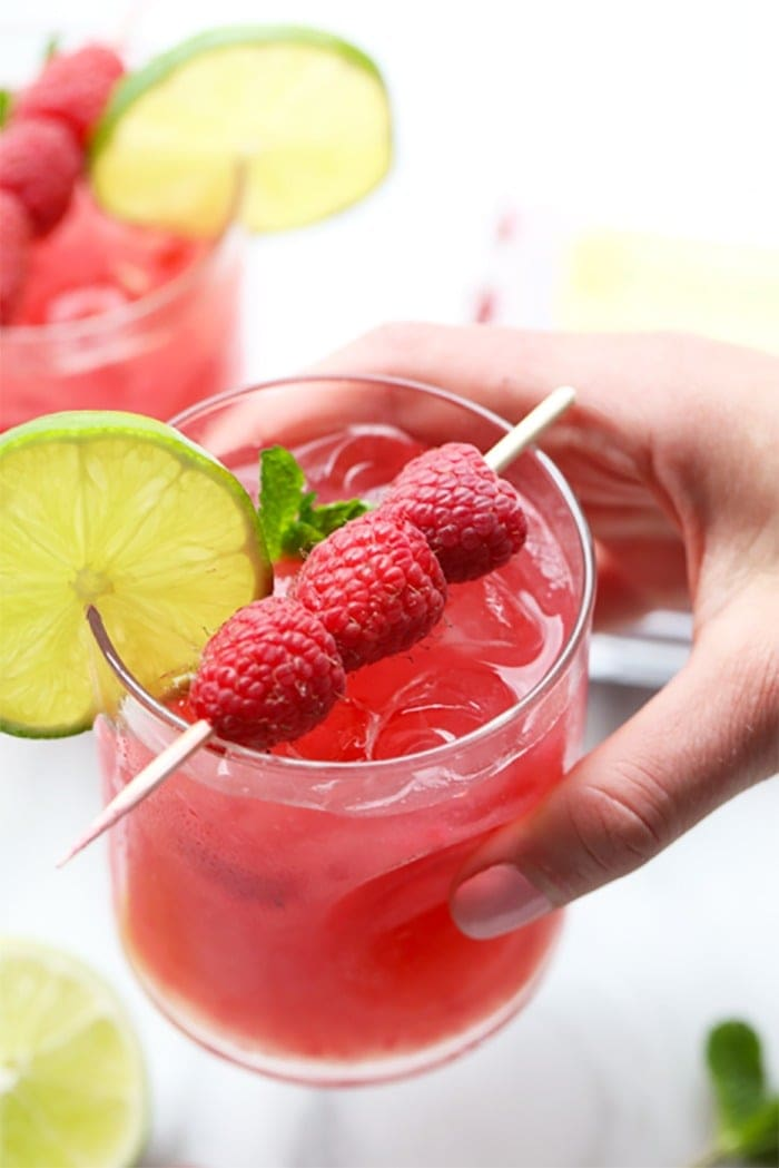 A hand holding a raspberry ginger mojito