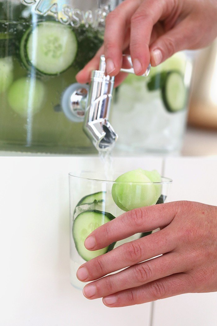 cucumber vodka drinks being dispensed in glass