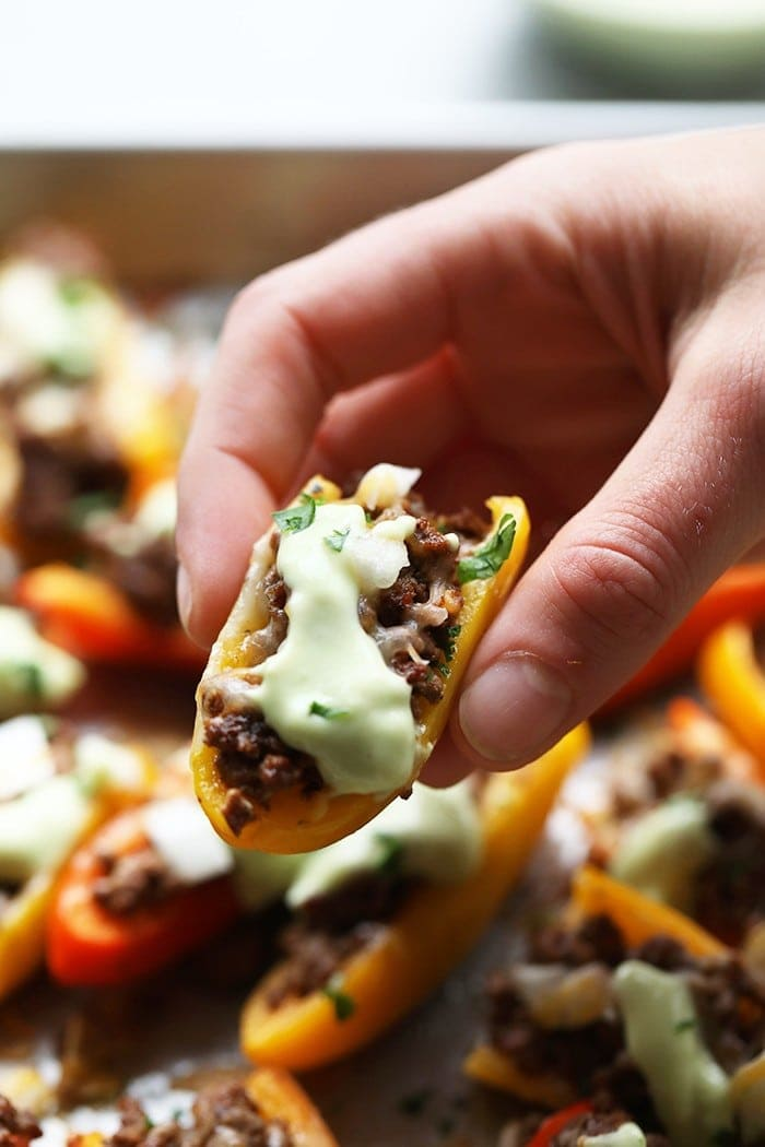 "Ditch the chips for a healthier nacho and use mini bell peppers! These Fajita ""Nachos"" are cute, delicious, and healthy. They're made with mini bell peppers, lean ground beef, and avocado crema."