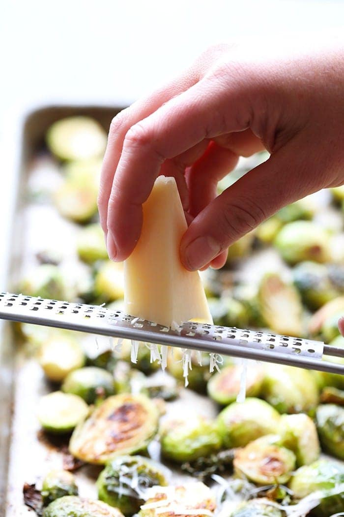 grating parmesan cheese onto brussel sprouts