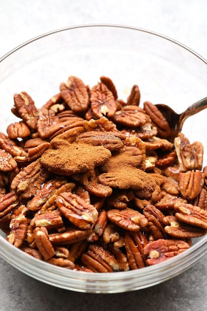 Fried maple pecans with cinnamon in a mixing bowl.