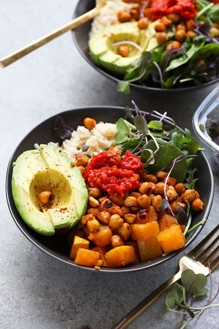 These Butternut Squash Buddha Bowls are the most colorful meal you'll ever eat! They're made with sprouted brown rice, crunchy chickpeas, roasted butternut squash, greens, avocado, and harissa sauce.