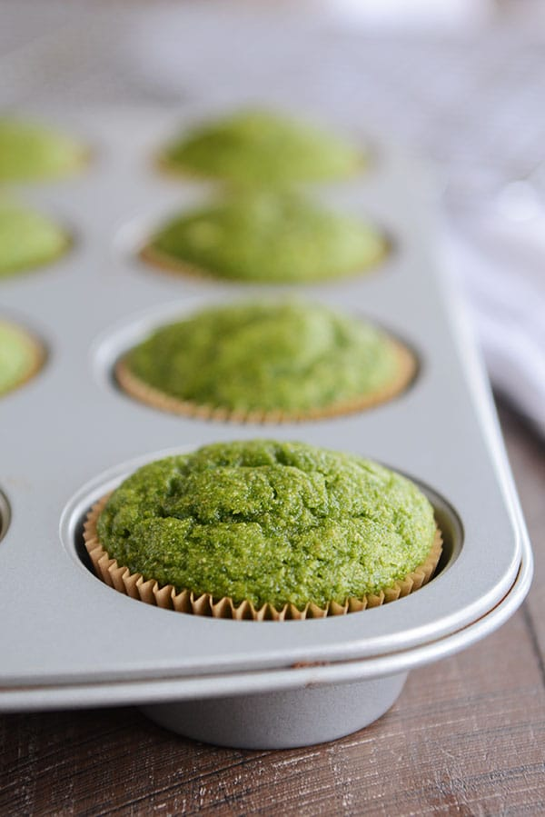 Green muffins in a muffin tin after being baked.