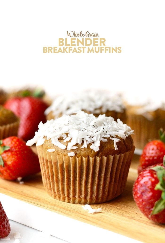 Whole grain blender breakfast muffin with coconut flake topping surrounded by strawberries.