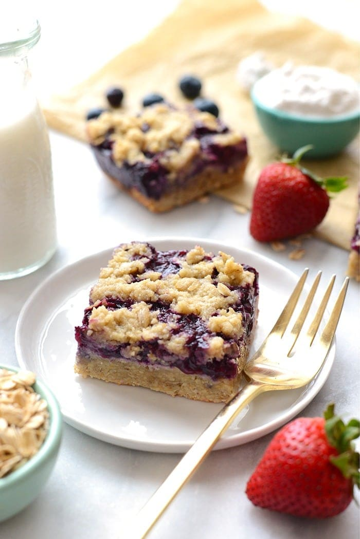 triple berry crumble bar on a plate with a fork