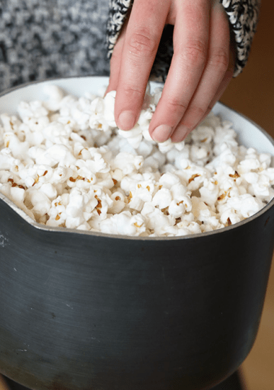 popcorn in pot with hand reaching for a handful