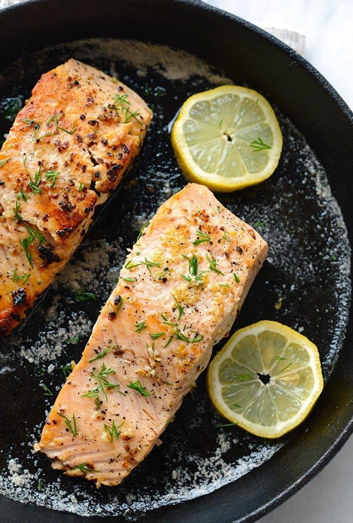 pan seared salmon with lemon in cast iron pan