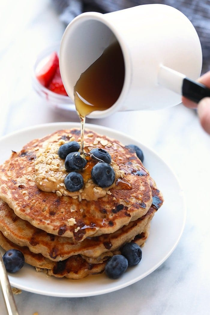 maple syrup pouring onto pancakes