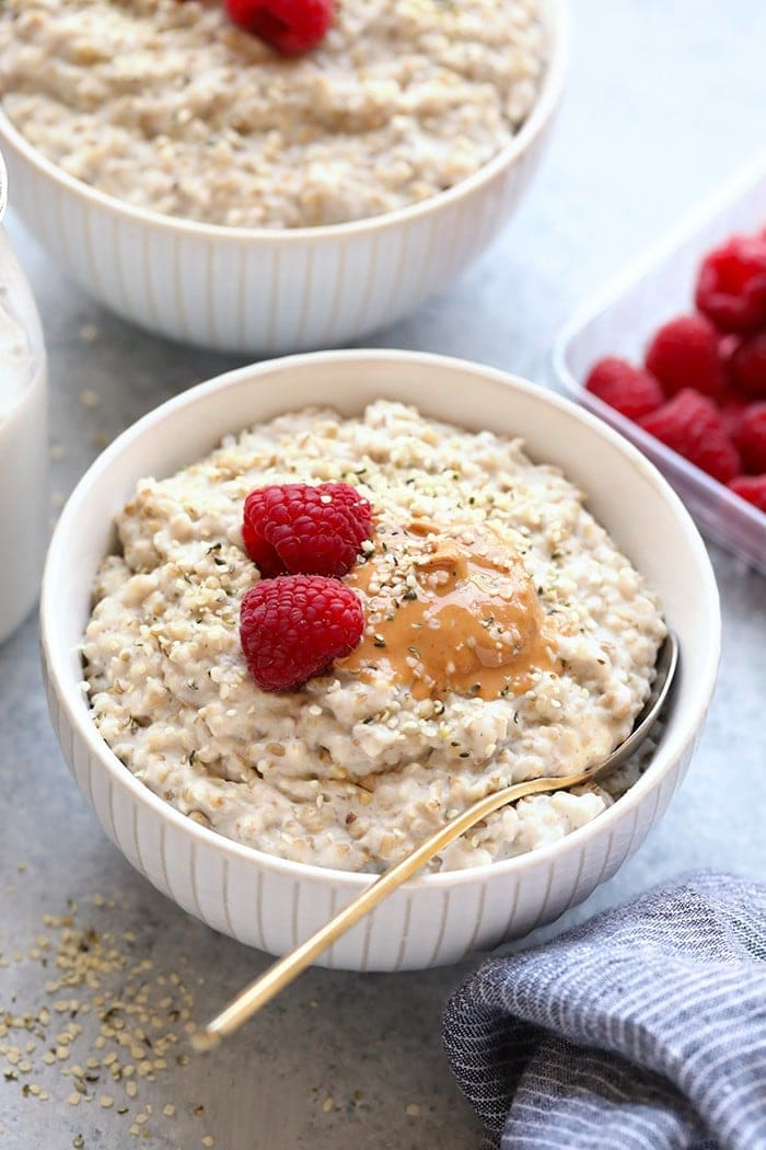 steel cut oats in bowl with nut butter and raspberries