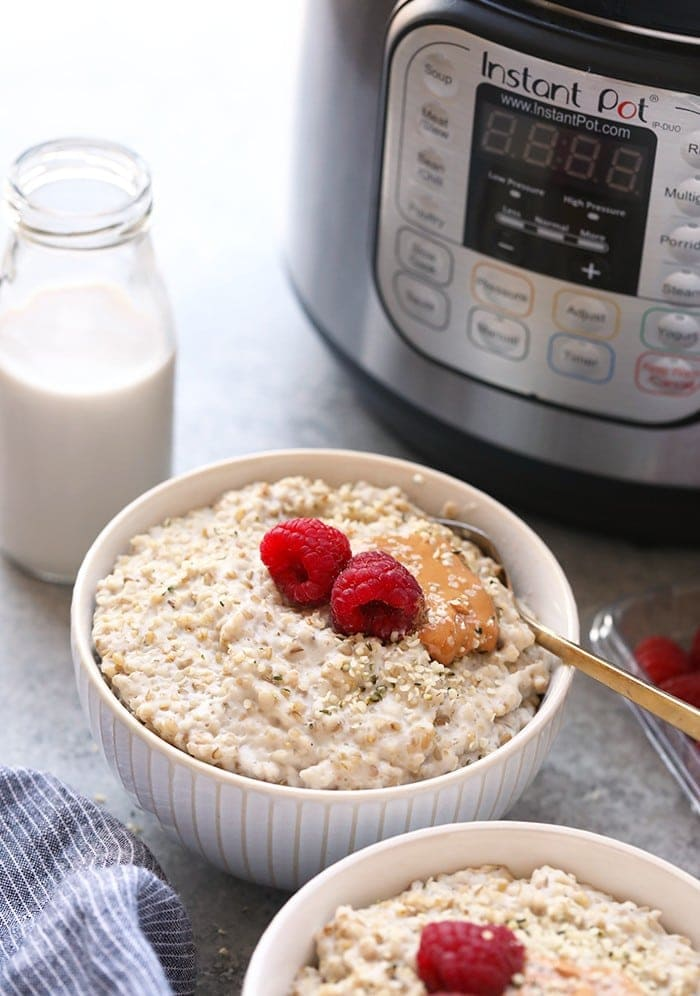 Instant Pot steel cut oats in a bowl next to the Instant Pot