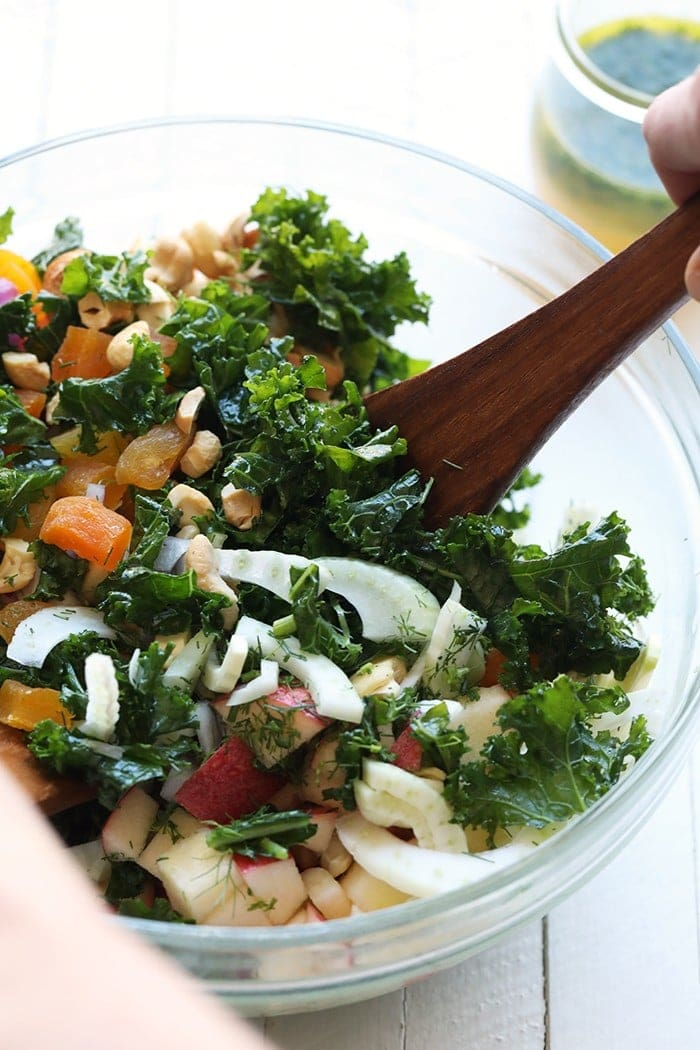 Mixing the massaged kale salad in a bowl.
