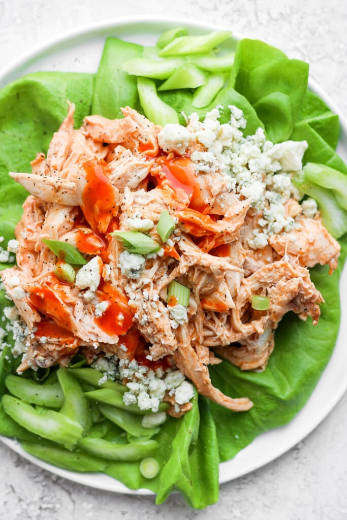 Shredded buffalo chicken in a lettuce wrap with blue cheese, celery, and green onions.