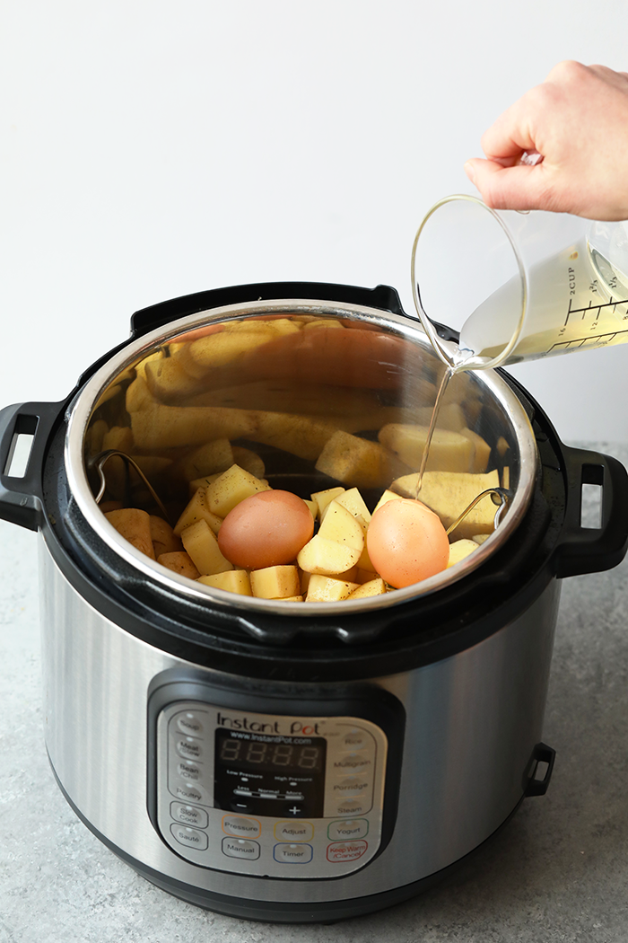 Pouring vinegar into the instant pot over potatoes