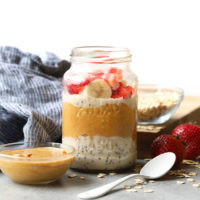 Overnight oats in a jar topped with peanut butter, strawberries and bananas.