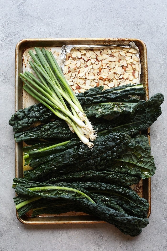 Cookie sheet with kale, green onions, and almonds
