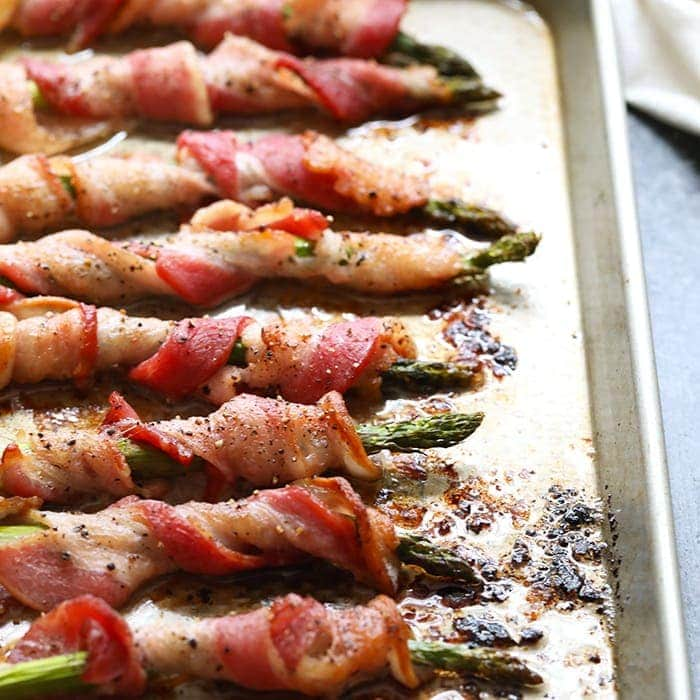 This bacon wrapped asparagus is a fun way to dress up your favorite veggie! You can make this bacon wrapped asparagus recipe for a tasty side dish for dinner or you can make them for an easy appetizer for a party. Either way, they're delicious!