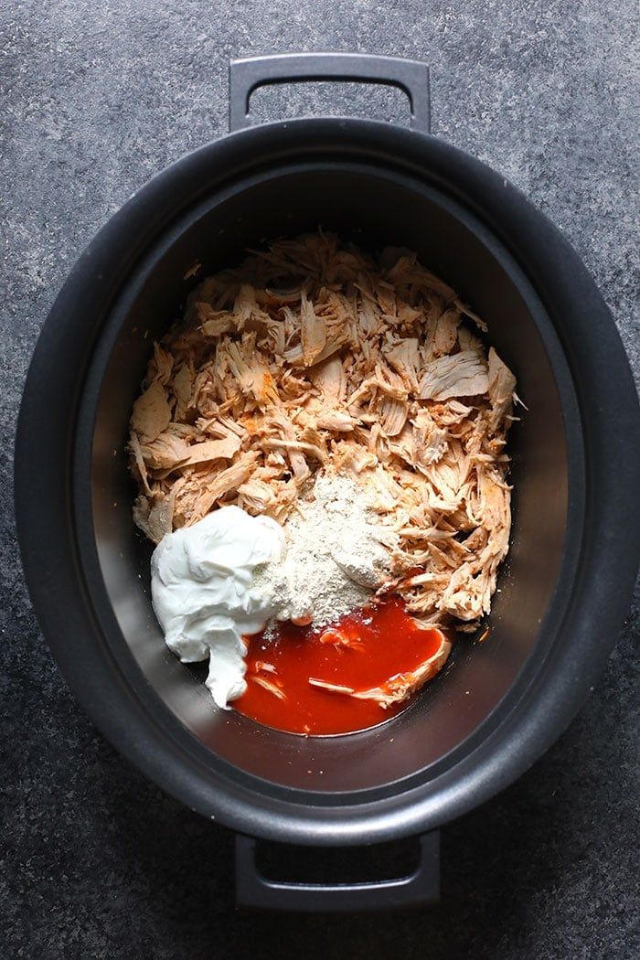 Ingredients for buffalo chicken dip on a slow cooker