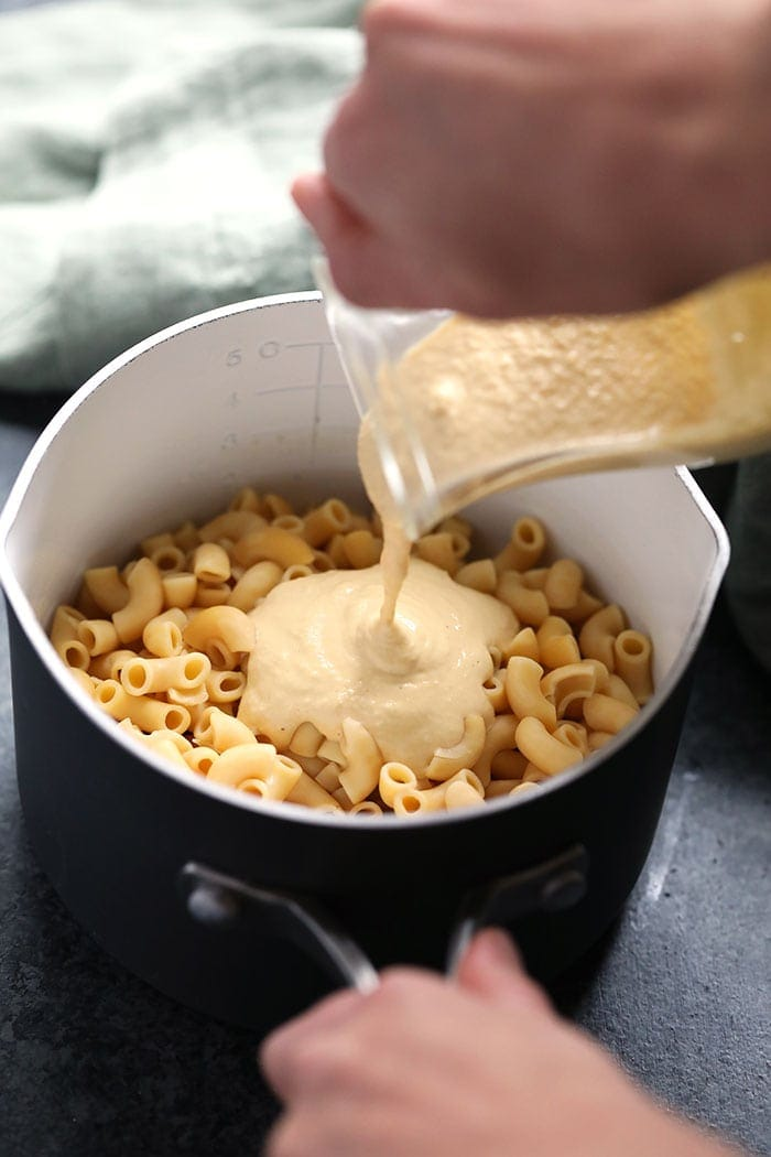 vegan mac and cheese sauce being poured over noodles