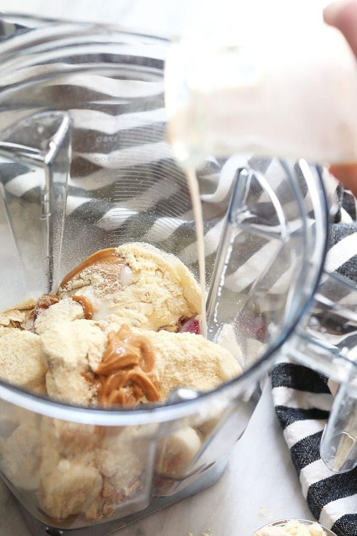 Pour healthy breakfast shake ingredients in Vitamix