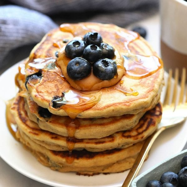 We've got an easy blueberry protein pancakes recipe for you that's made with 100% whole grains, your favorite protein powder, mashed banana, and blueberries! You'll never use another protein powder pancakes recipe again.