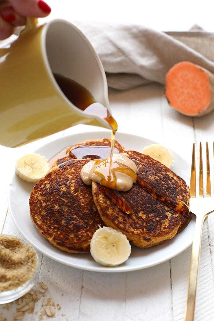 Pouring maple syrup on sweet potato pancakes