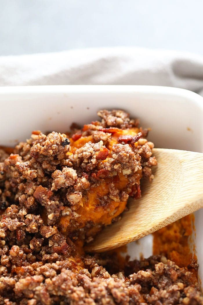 sweet potato casserole being scooped from the baking dish with a spoon