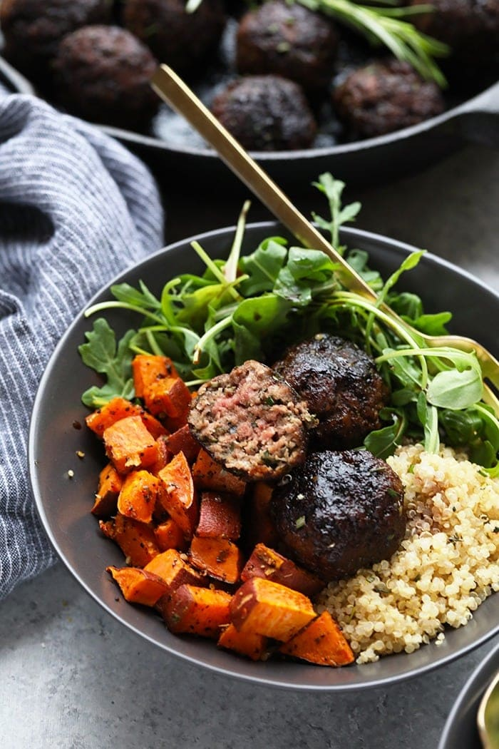 Rosemary Thyme Balsamic Meatballs in a bowl with quinoa, sweet potatoes, and arugula