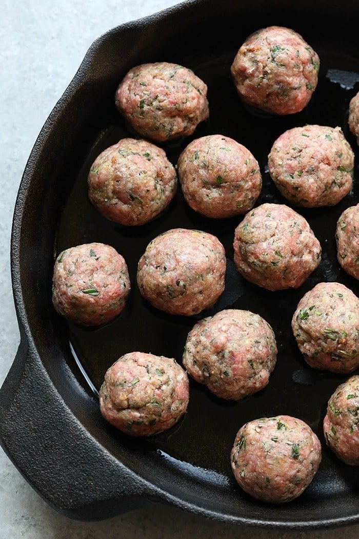Raw meatballs in a cast iron pan