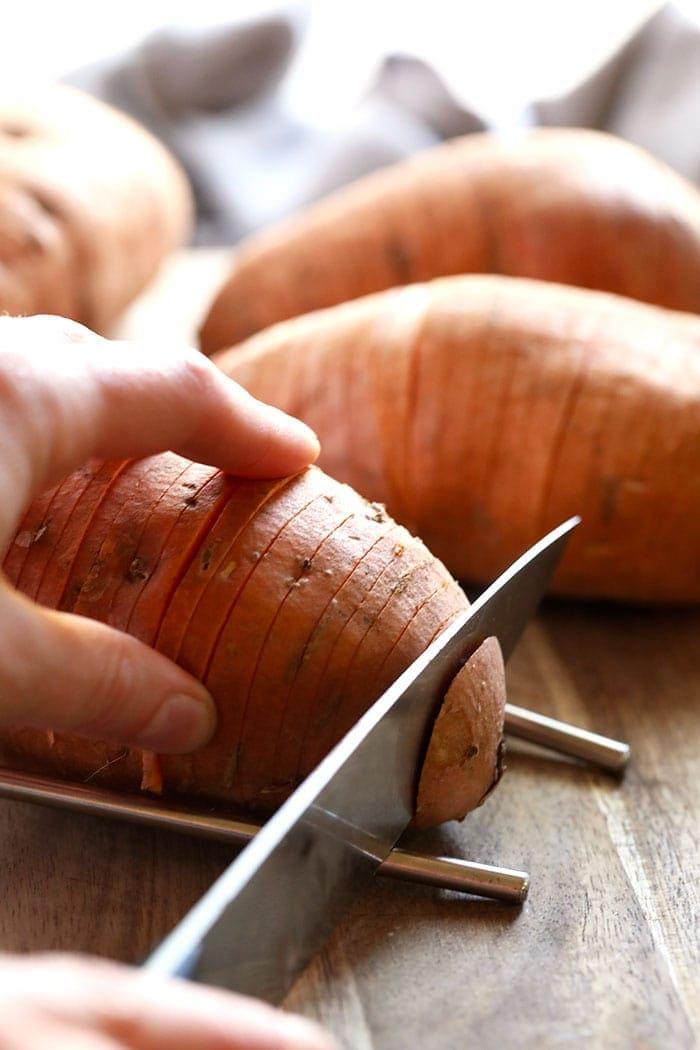 sweet potato being cut hasselback style