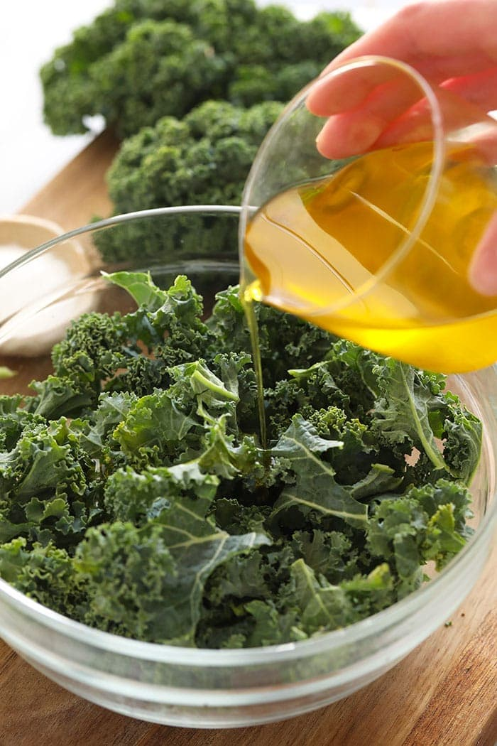 Pouring olive oil over kale
