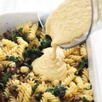 Pouring vegan pasta sauce into a casserole dish