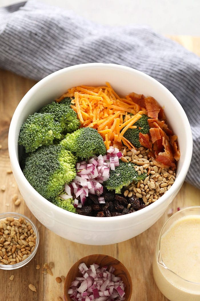 Ingredients for healthy broccoli salad with bacon in a bowl