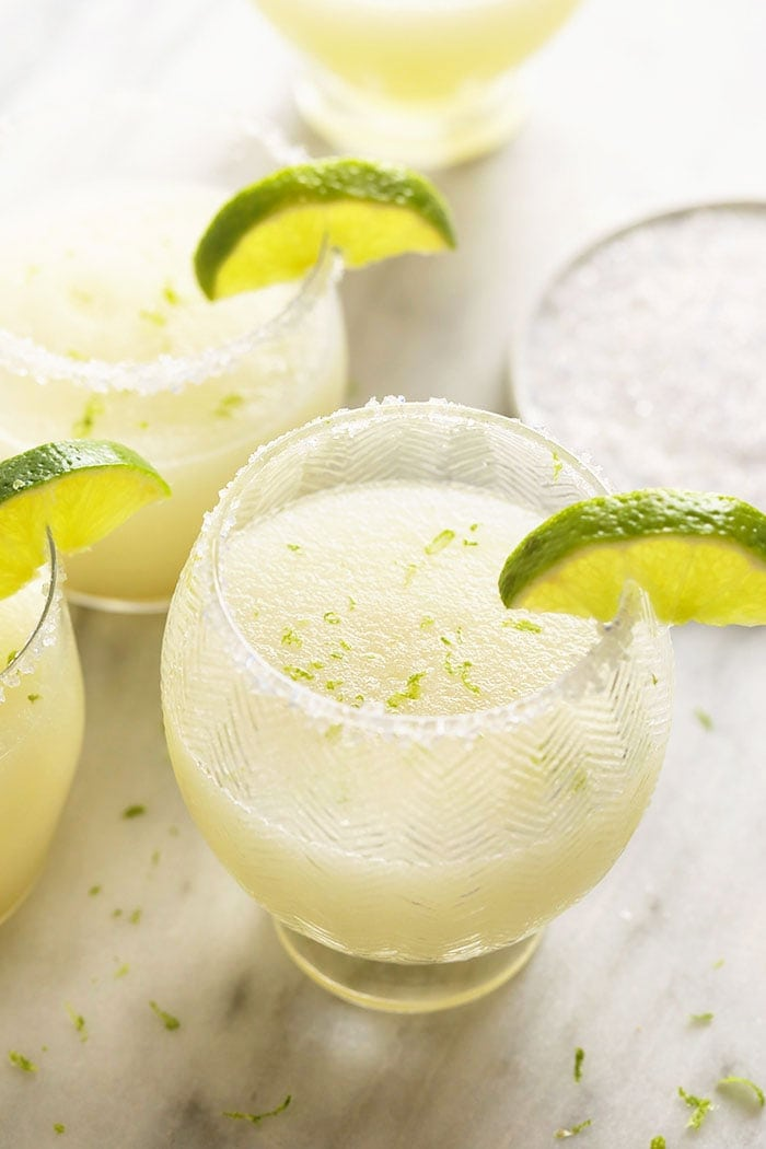 Frozen Margaritas in glasses with limes