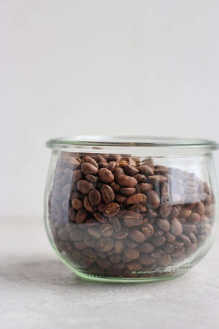 A clear container with coffee beans in it
