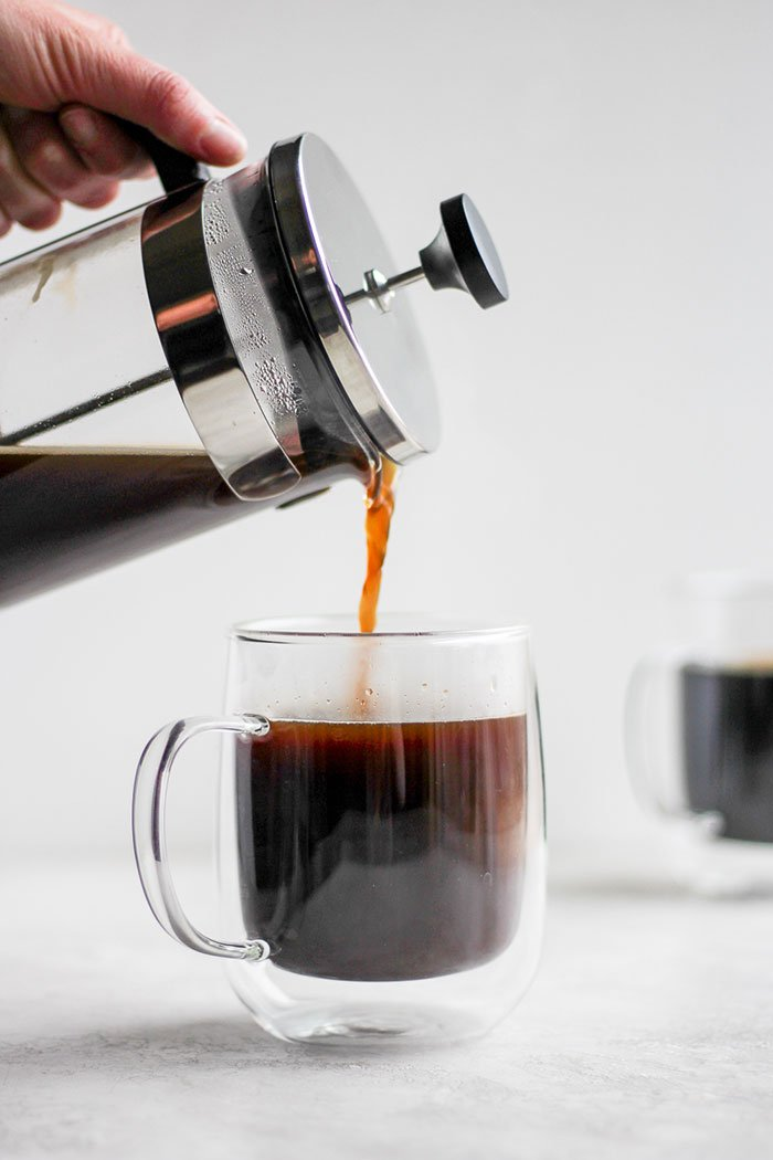 Pouring coffee from a french press into a mug