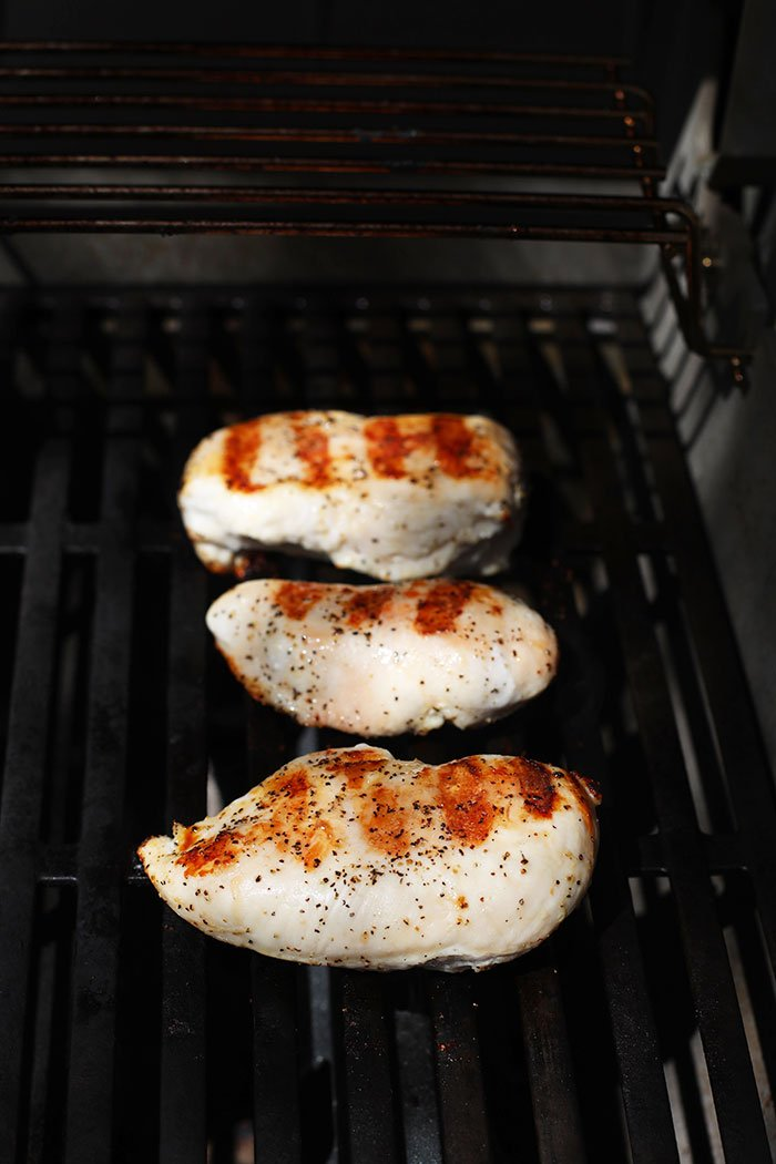BBQ grilled chicken breast on the grill.