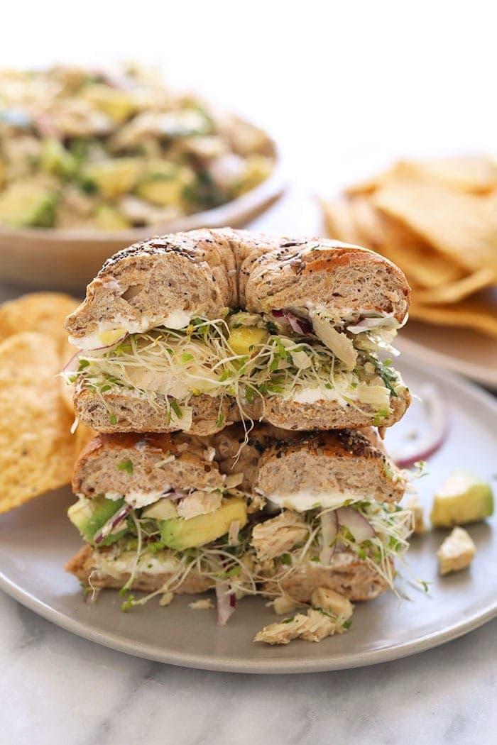 avocado tuna salad sandwich on a bagel on a plate