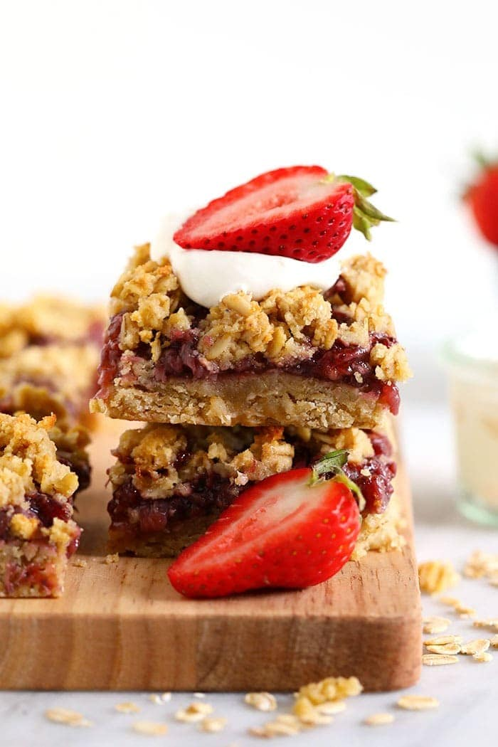 healthy strawberry oatmeal bars stacked and topped with fresh strawberries