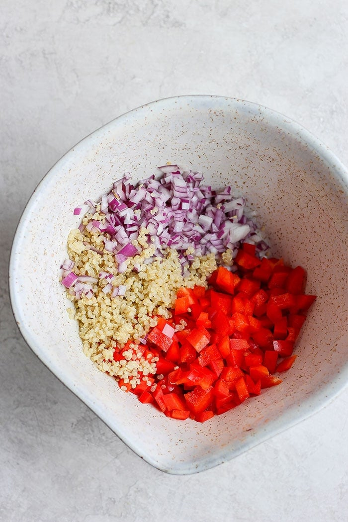 Red onion, quinoa, and red pepper in a bowl