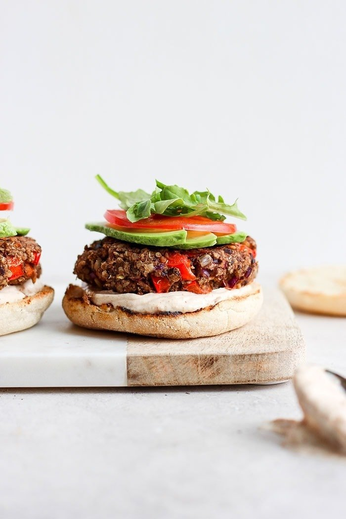 quinoa burgers on an english muffin with sauce, avocado, tomato, and arugula