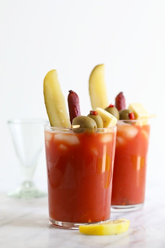 Bloody mary in a glass with pickles, olives, and cheese