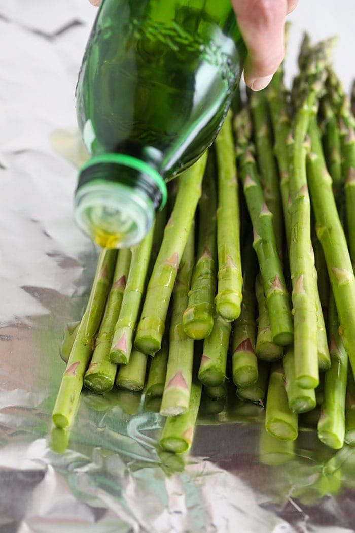 drizzling olive oil on asparagus