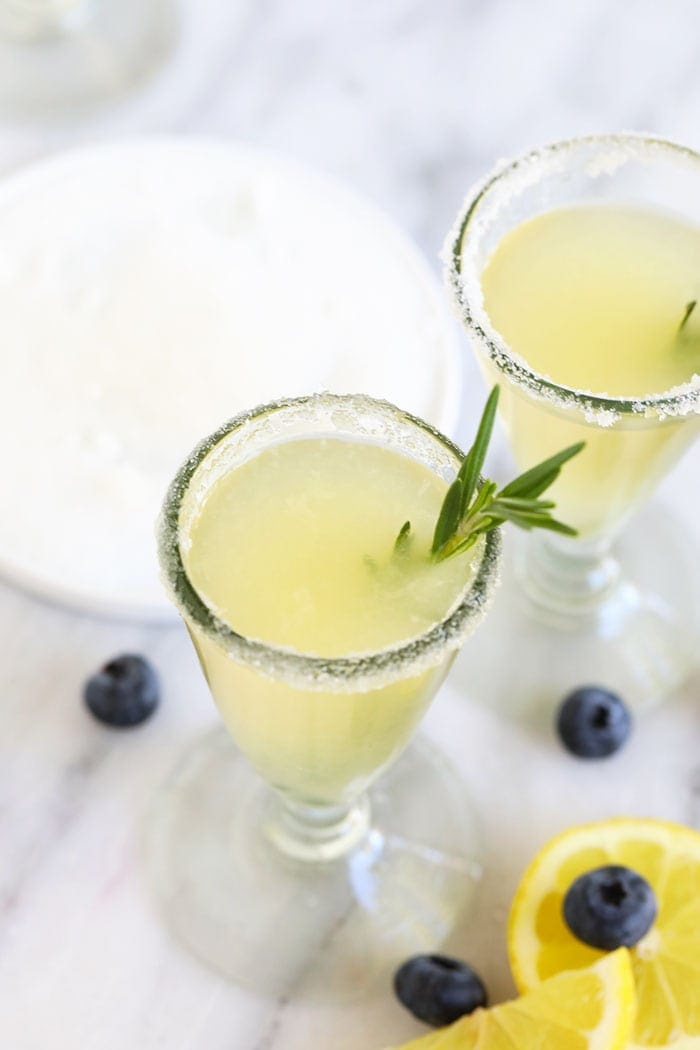 lemon drop martini in a glass with rosemary garnish