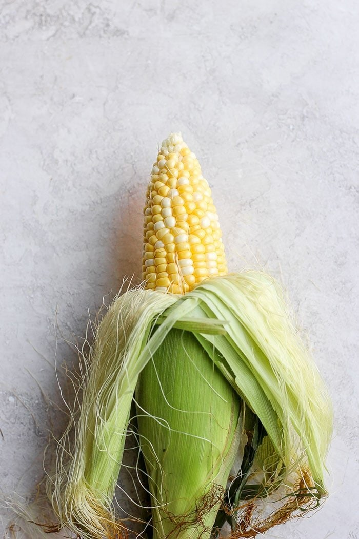 Half shucked corn on the cob