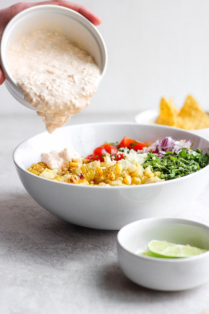 Pouring sauce onto the Mexican Street Corn Salad