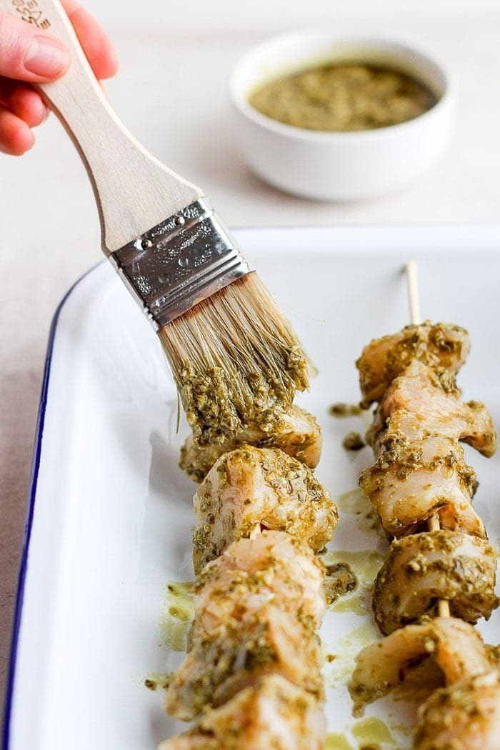 wiping pesto onto chicken skewers