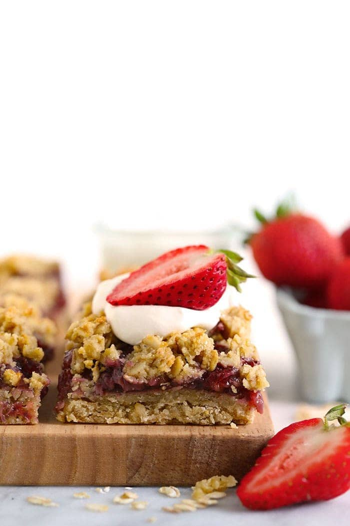 strawberry oatmeal bar sliced and topped with whipped cream and a sliced fresh strawberry