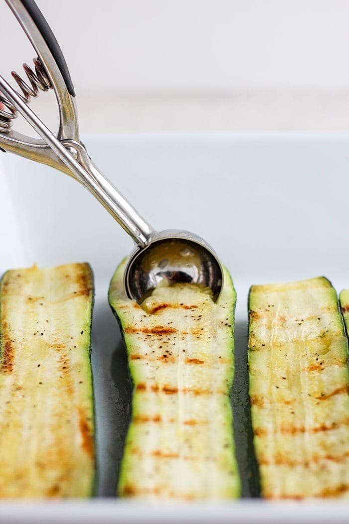 sliced zucchini being scooped with a melon baller