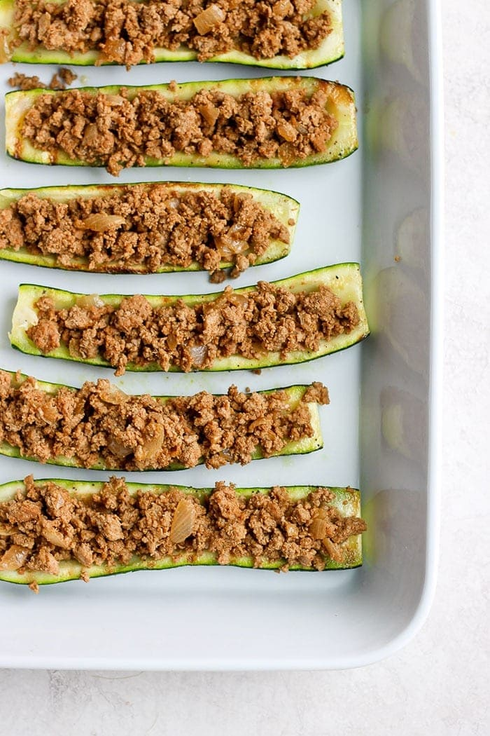 taco zucchini boats ready to be topped with cheese and finished on the grill