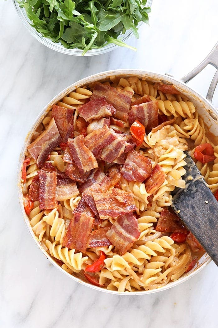 chopped bacon being mixed into a BLT pasta